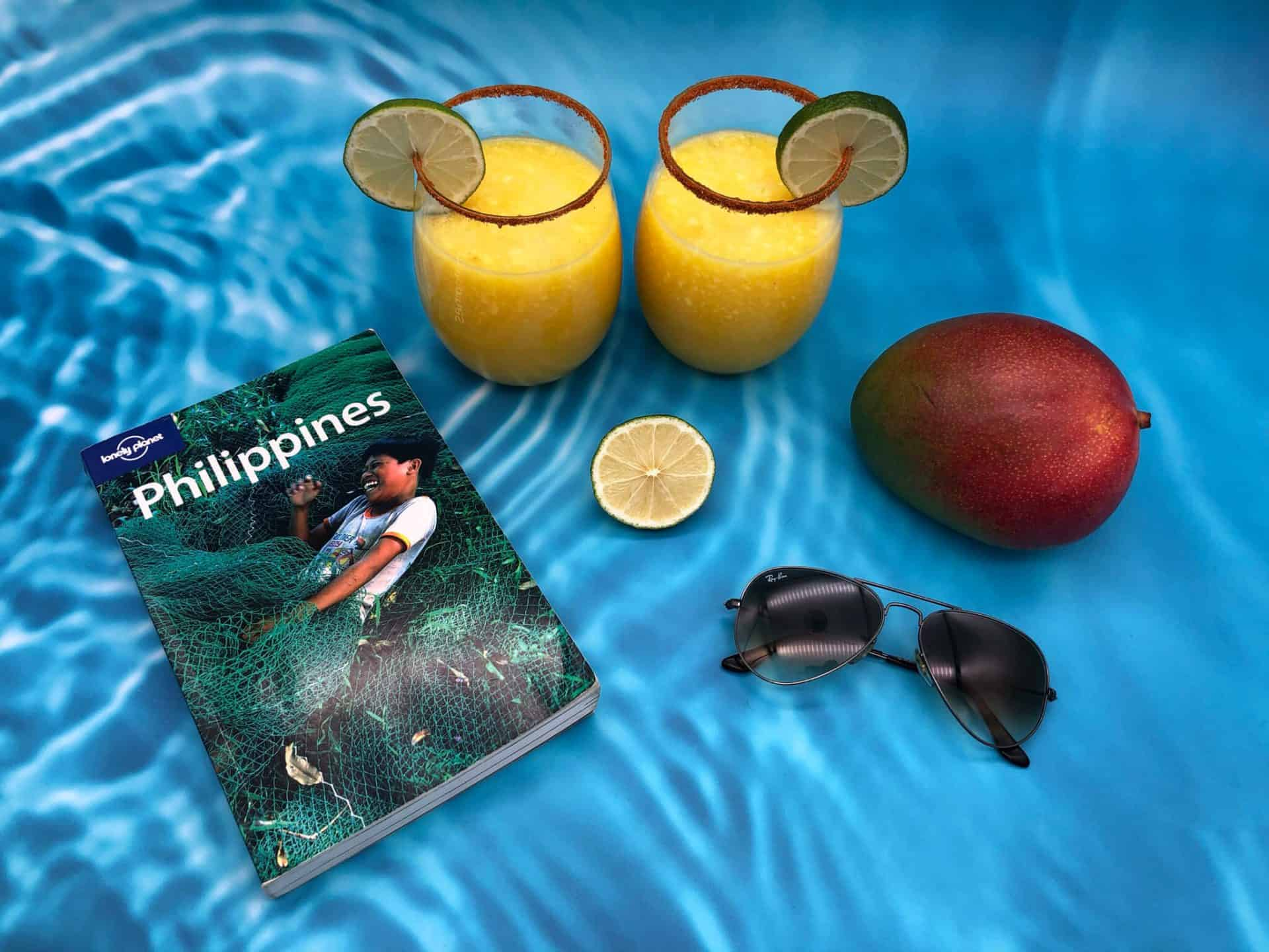 Holiday mocktails with mango, lime, sunglasses and travel book