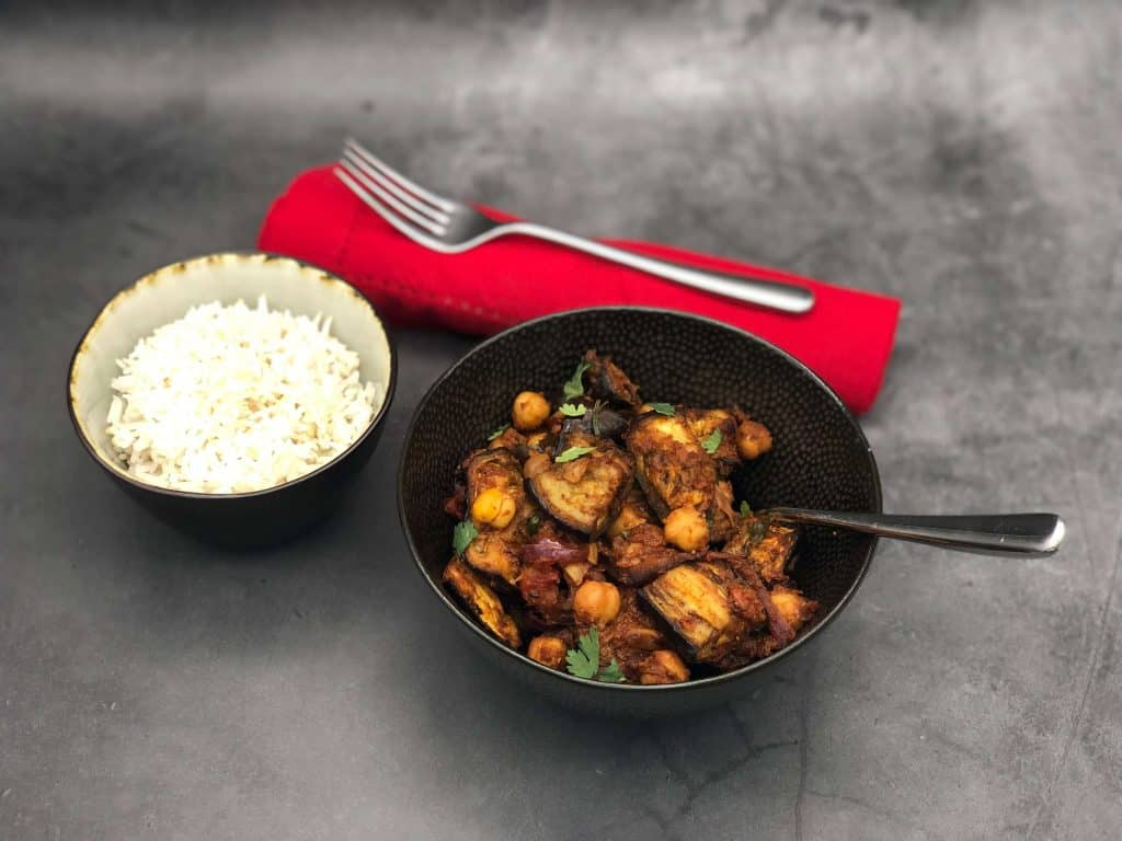 Aubergine curry in a bowl with rice and a fork