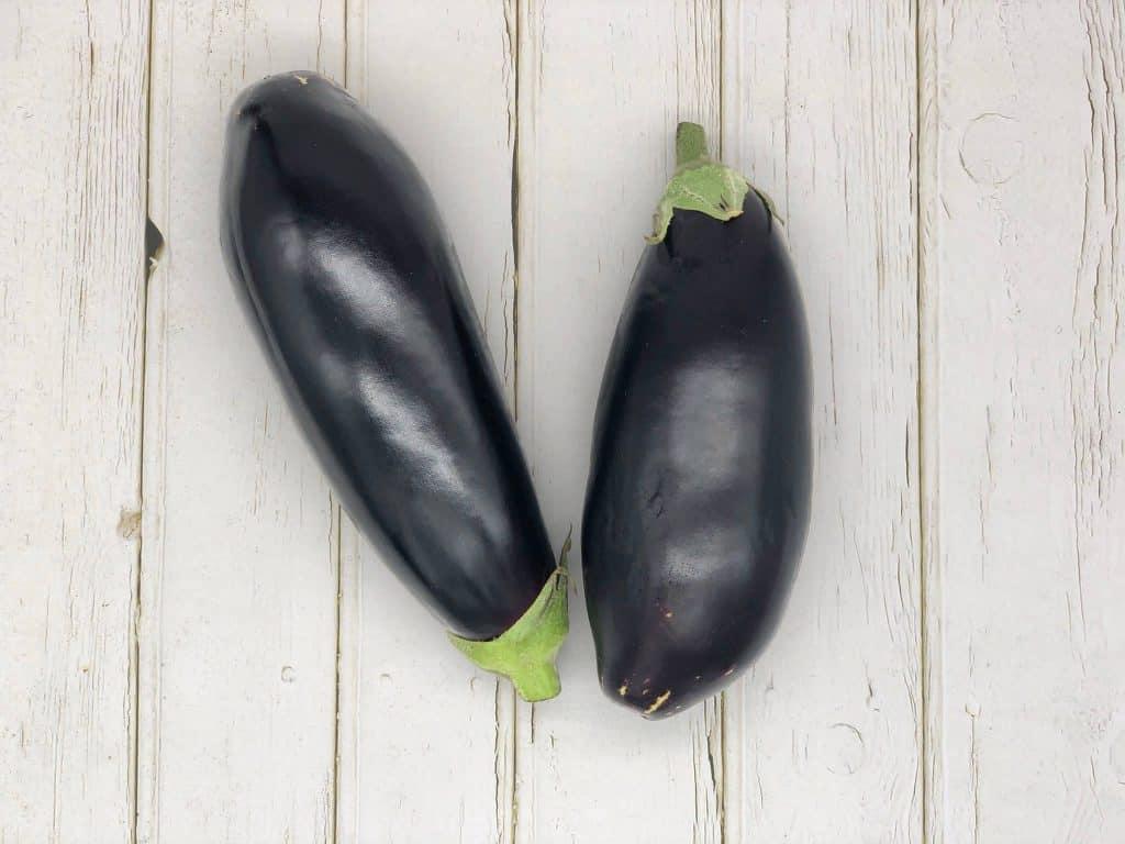Two fresh aubergines eggplants on wood