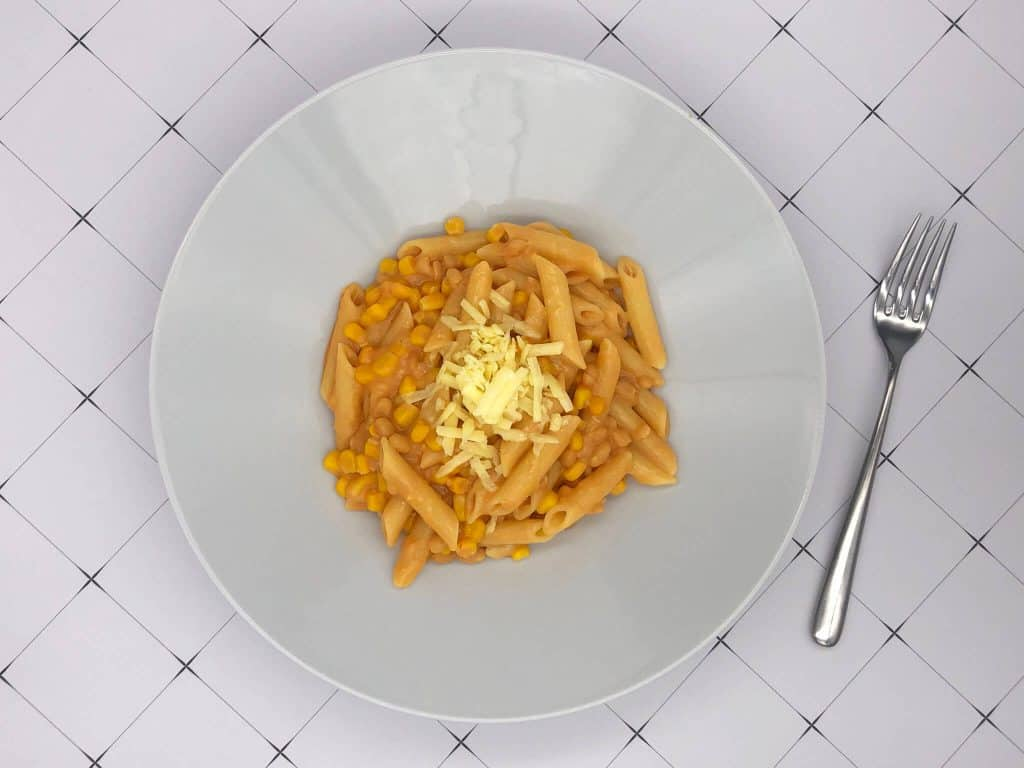 Baked beans, penne pasta, sweetcorn and grated cheddar cheese store cupboard meal cooked and ready to eat