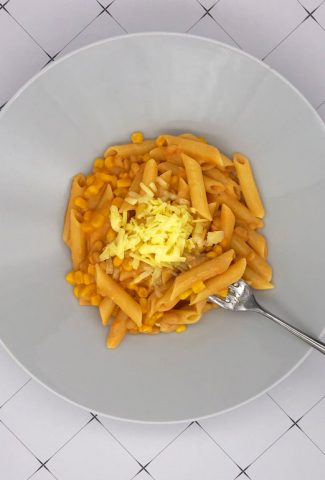 Hot cheesy beans and sweetcorn on penne pasta in a bowl and a fork