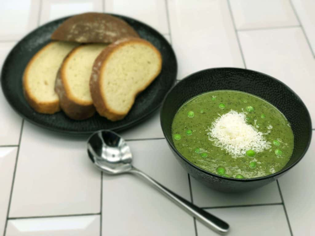 Tasty pea and mint soup with bread and a spoon on a tile background