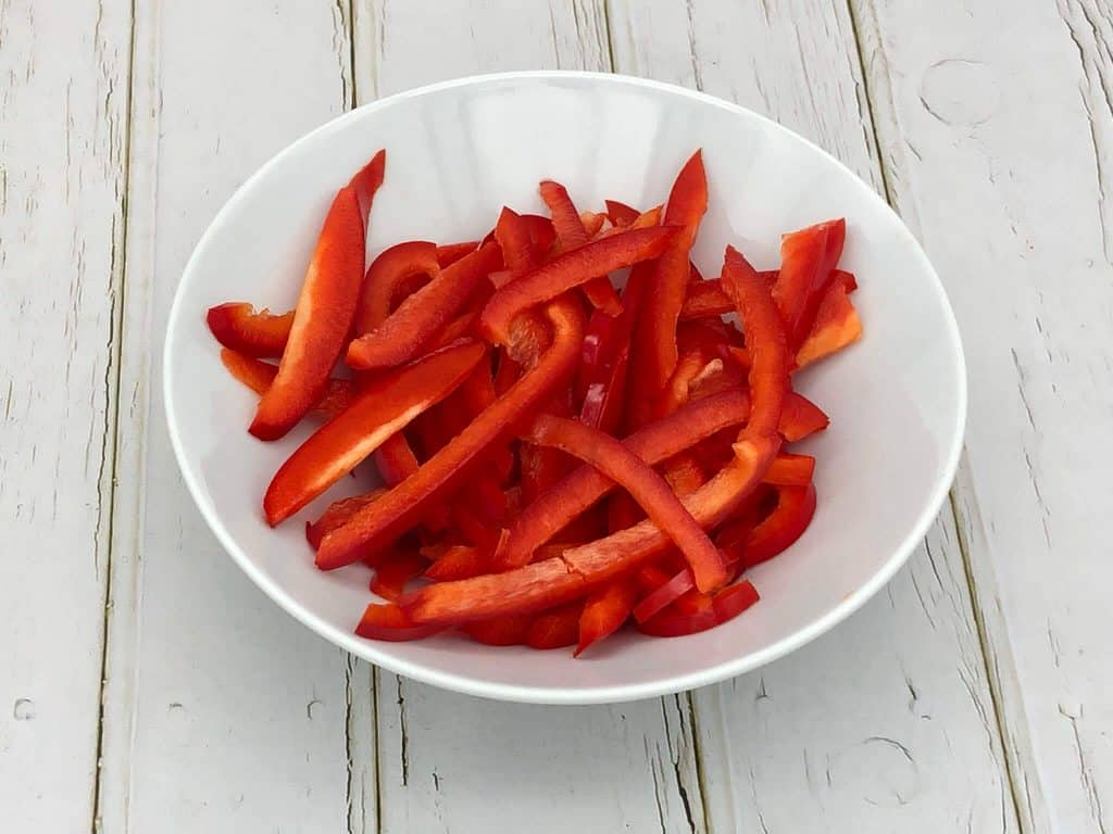 Sliced fresh red peppers in a white bowl