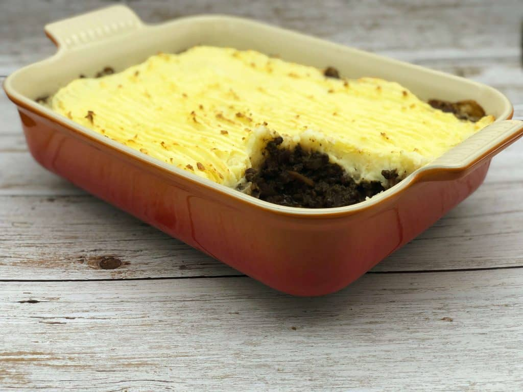 Vegetarian shepherds pie in an oven dish with a slice eaten