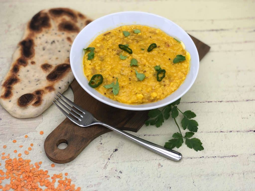 Tarka dhal on a wooden board with naan bread