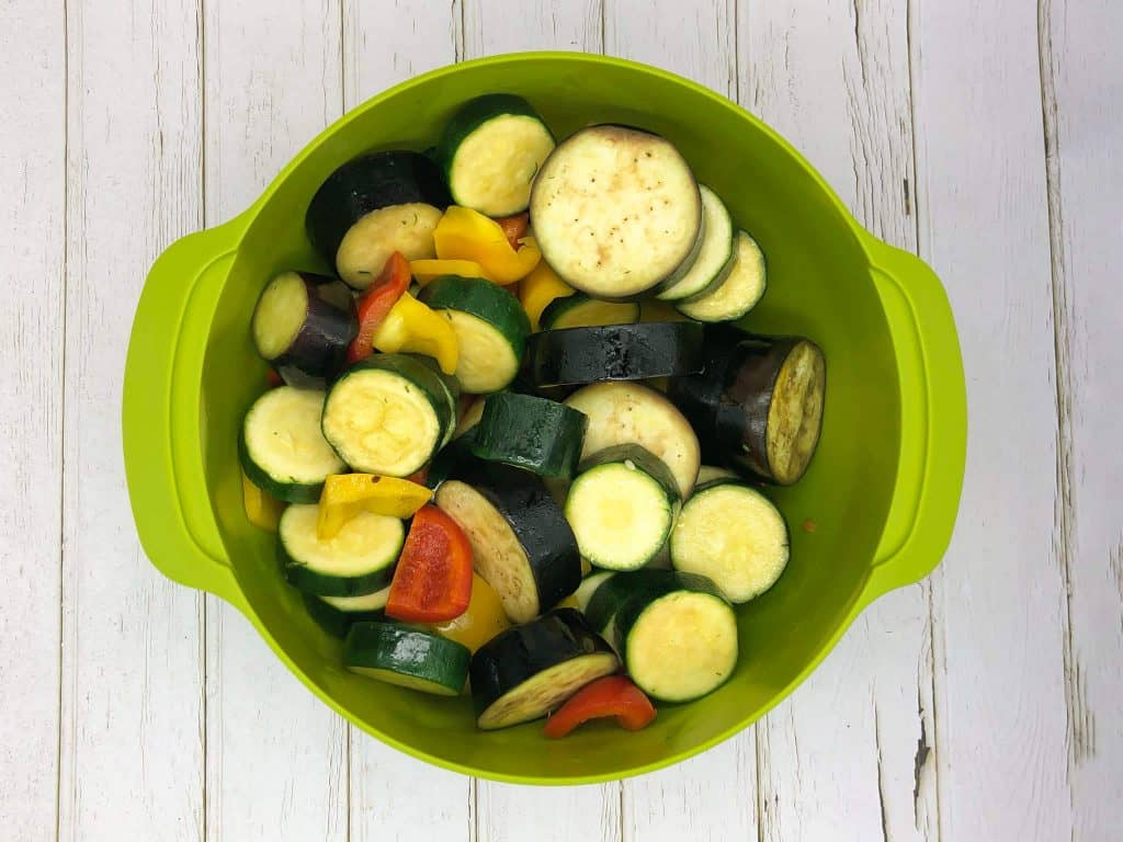A green bowl full of ratatouille ingredients