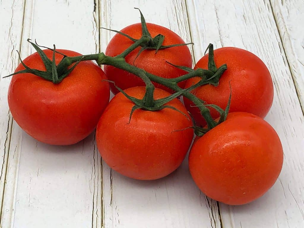 Five ripe tomatoes on the vine