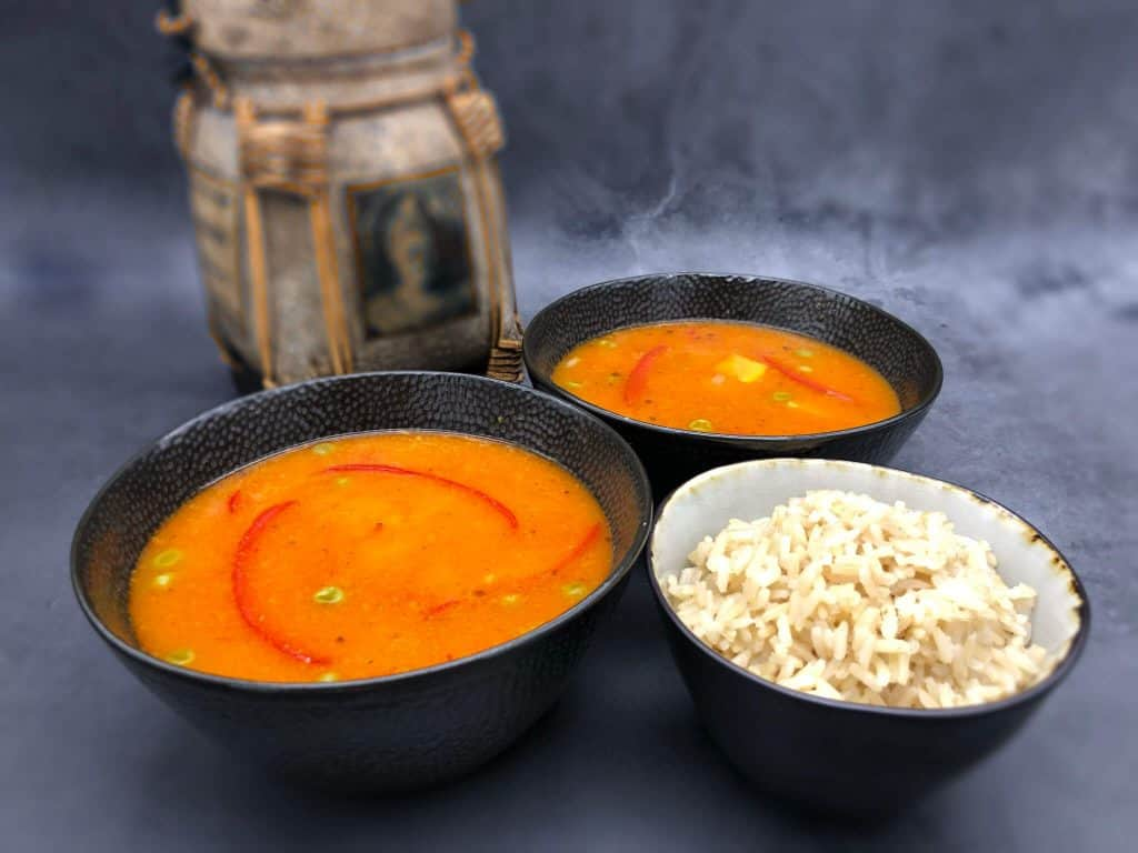 Two bowls of red Thai curry with rice and a rice container