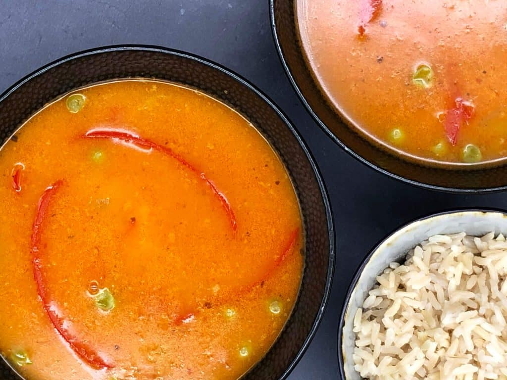 Red pepper and peas gloating in bowls of tasty Thai red curry and a bowl of rice