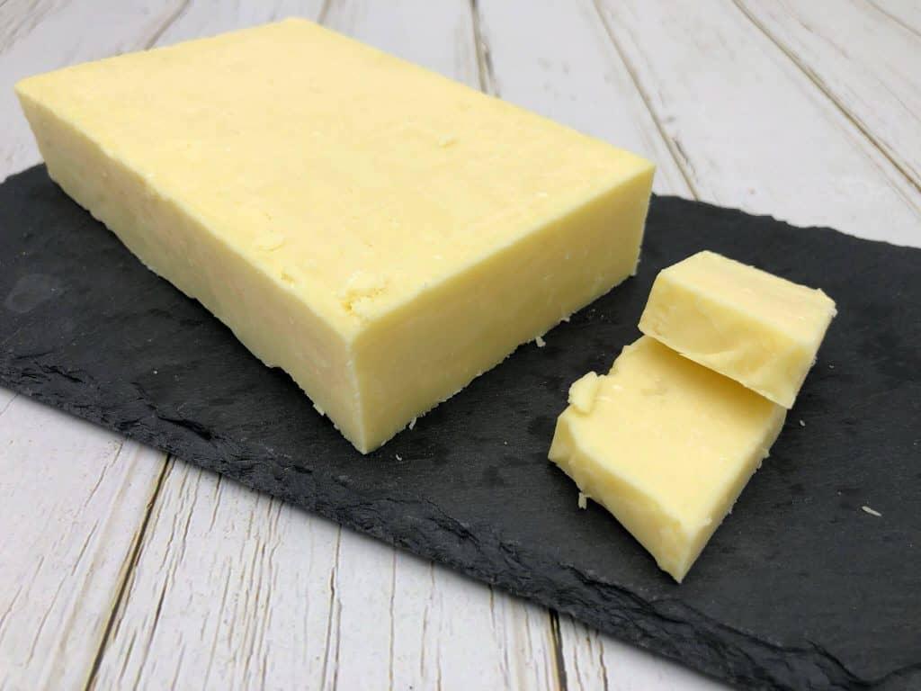 Cheddar cheese slab on a black slate