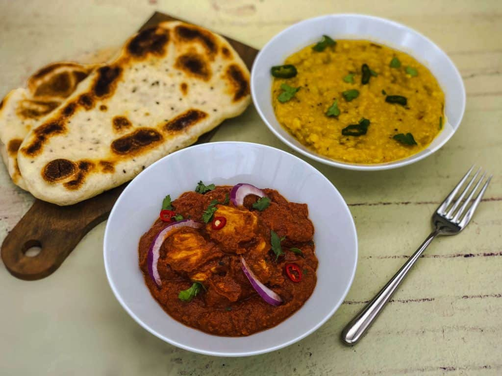 Homemade chicken madras, tarka dhal and naan bread