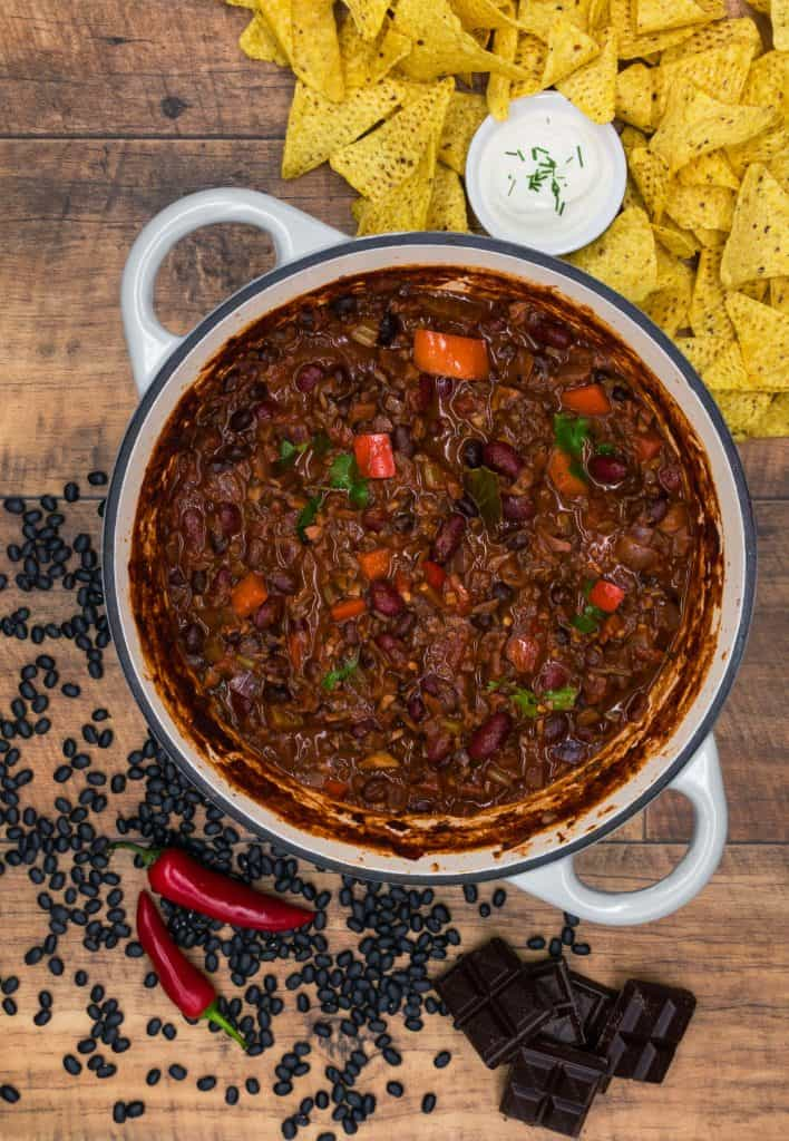 A Dutch oven of vegetarian chilli with tortilla chips, sour cream and chocolate