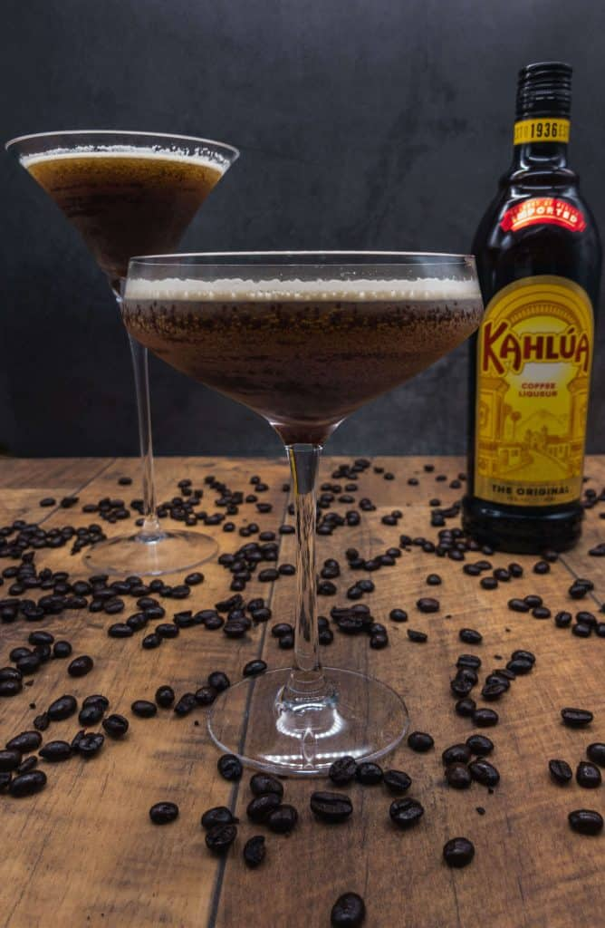 Two espresso martini cocktails and a bottle of kahlua