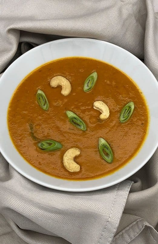 A white bowl filled with mulligatawny soup