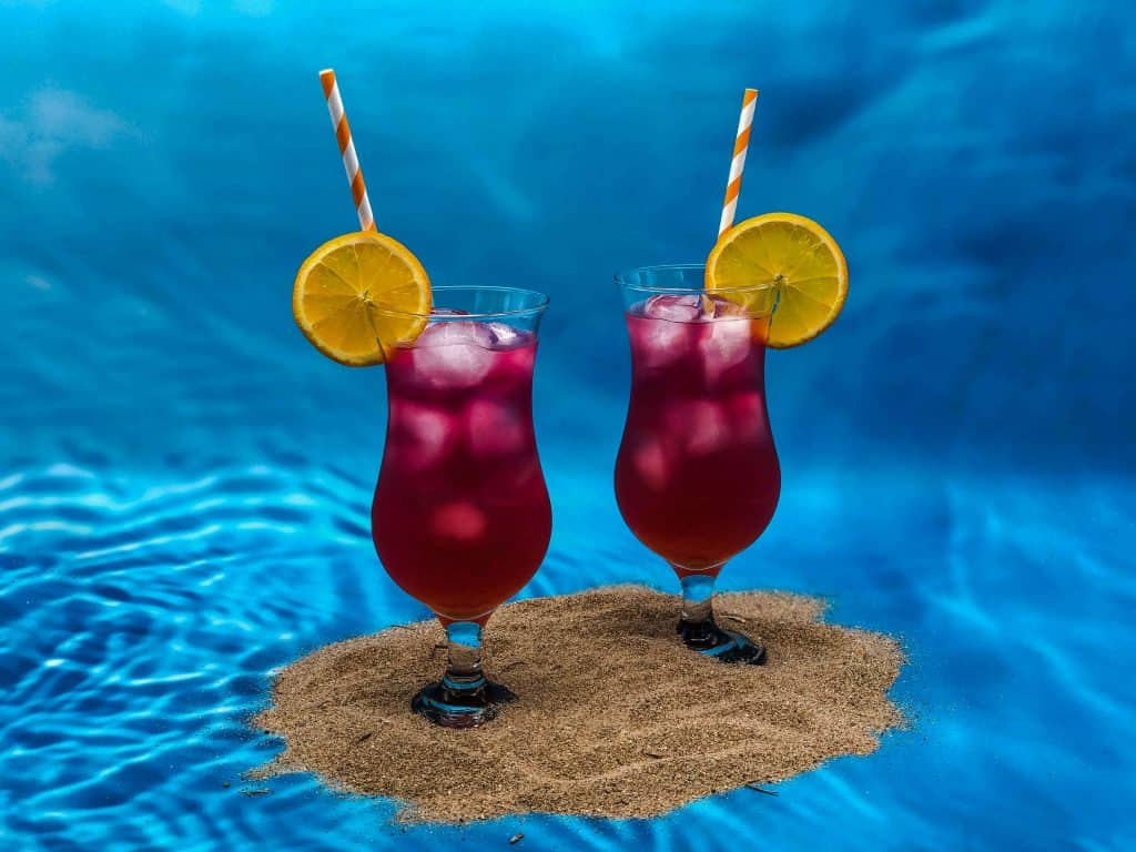 Two Sex on the Beach cocktails standing on beach sand