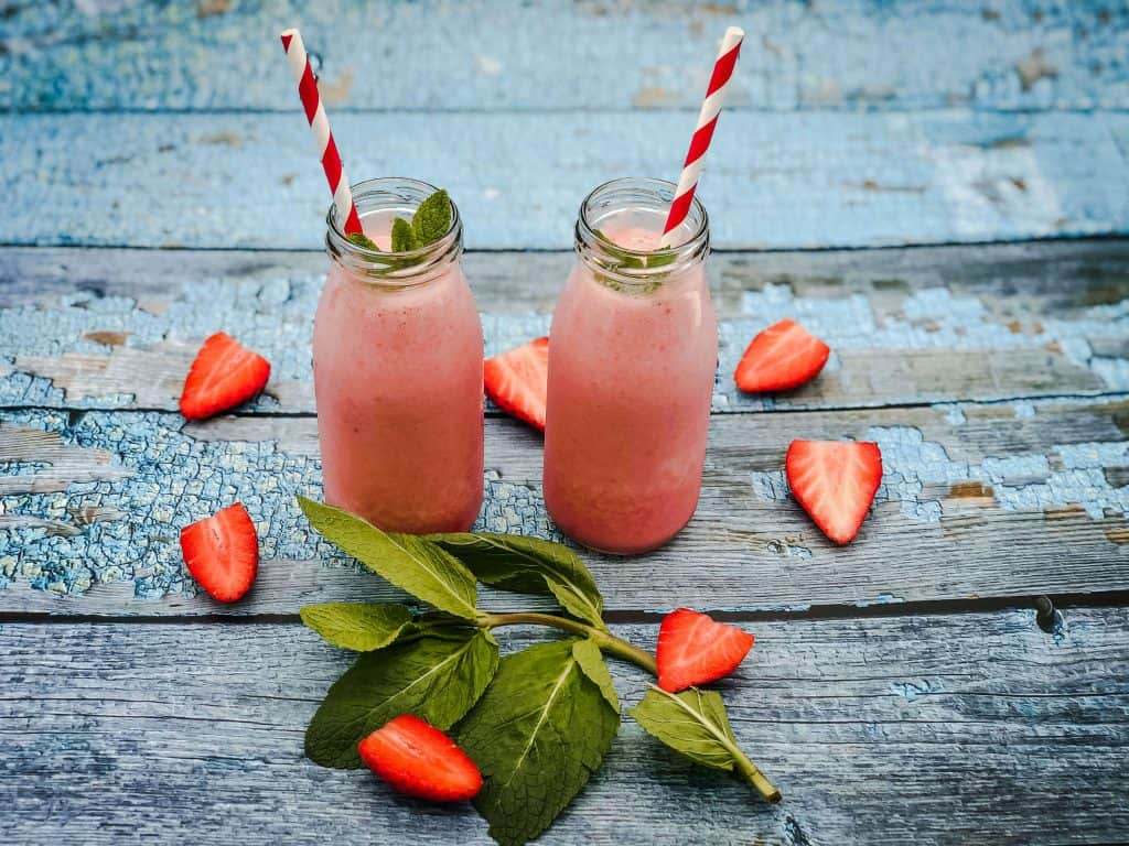 Two strawberry milkshakes on a blue wooden surface