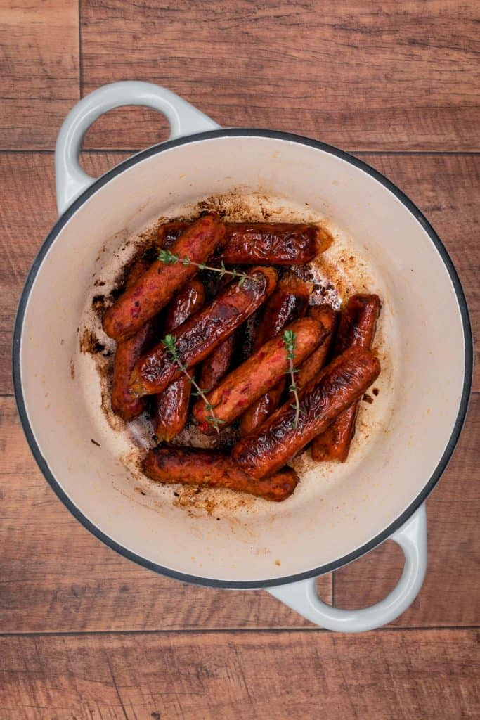 Vegetarian sausages cooking in a Dutch oven