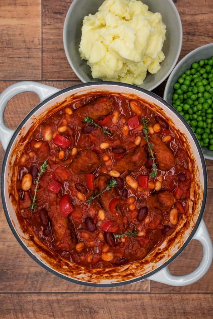 Vegetarian sausage and bean casserole with thyme, mashed potato and peas
