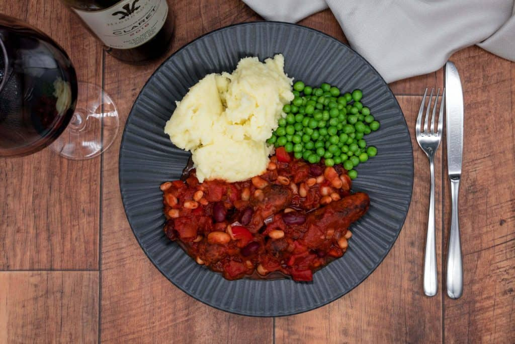 veggie bean and sausage casserole with mashed potato, peas and red wine
