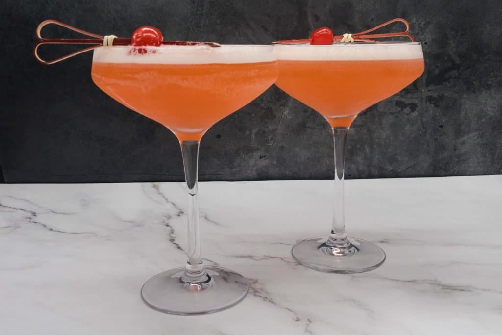 Two sour aperol cocktails with cherry garnish