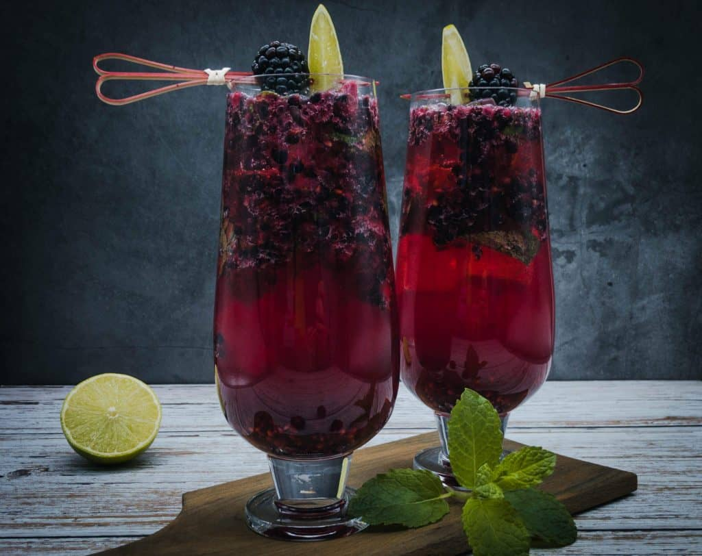 Two blackberry mojito cocktails with fresh lime and a mint sprig