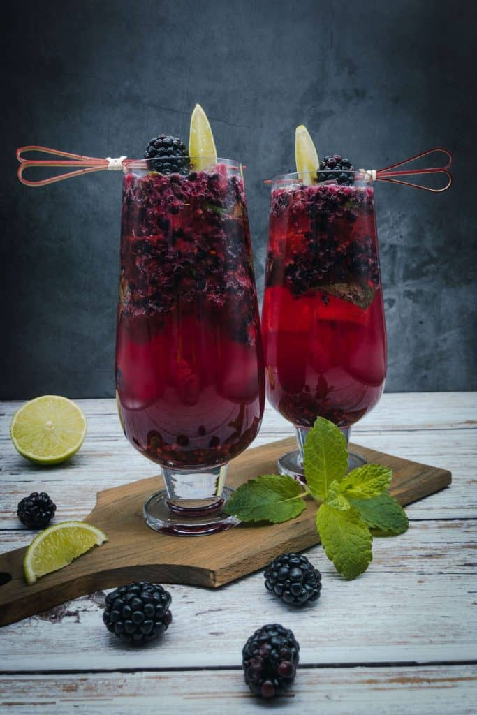 Two blackberry mojitos with blackberries, lime wedges and a sprig of mint