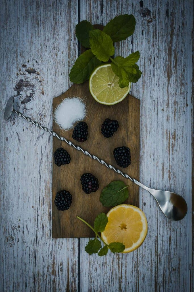 A wooden board with blackberries, lemon, lime, sprigs of mint and a muddling spoon