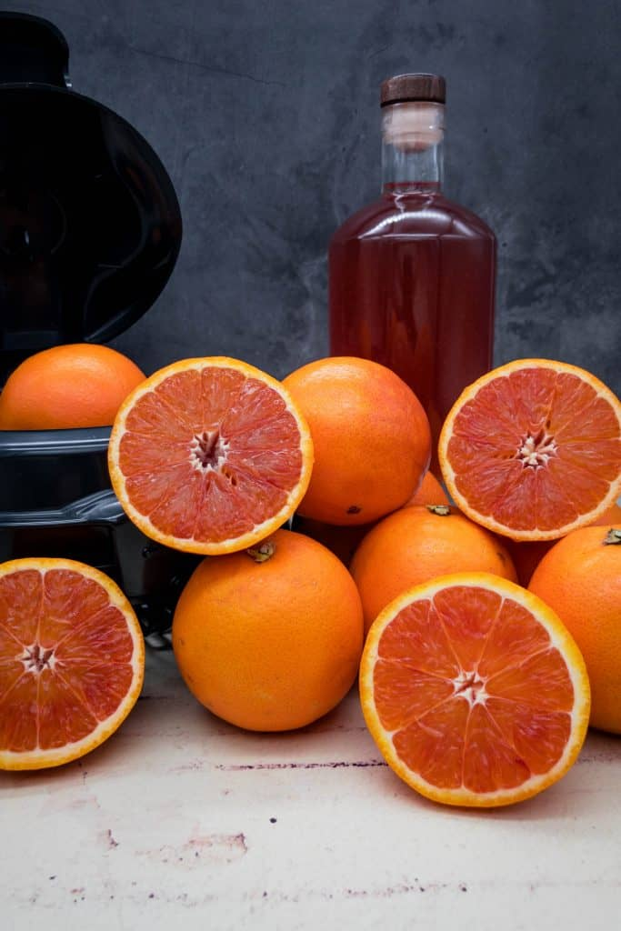 A bottle of homemade blood orange gin with blood oranges