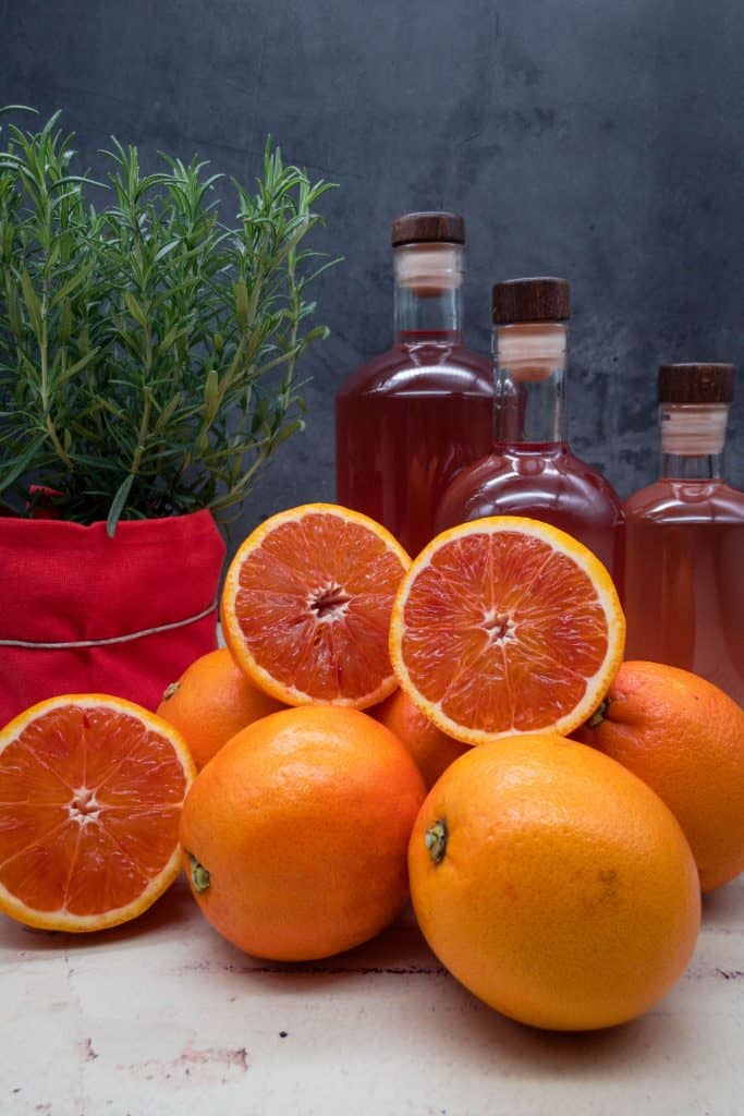 Three bottles of homemade blood orange gin, blood oranges and a rosemary plant