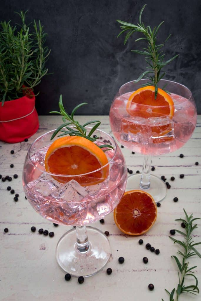 Two glasses of homemade blood orange gin and tonics with rosemary