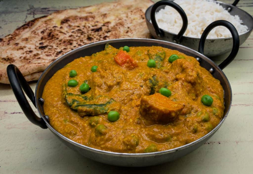 Mixed vegetable curry in a balti dish with rice and naan bread