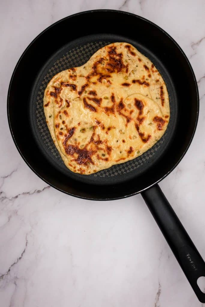 A delicious hot fresh Peshwari naan in the frying pan, cooked and ready to serve