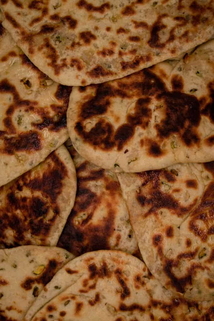 Lots of hot Peshwari naans freshly baked and ready to eat stuffed with desiccated coconut and almonds