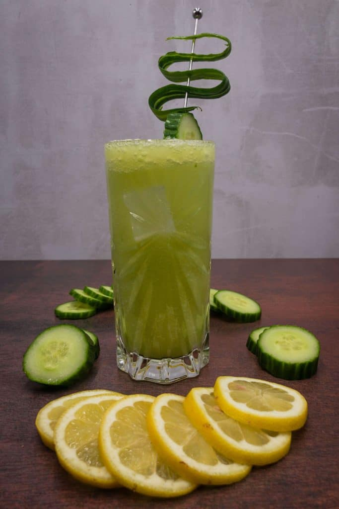 A highball glass full of Tom Collins mocktail with ice and cucumber garnish