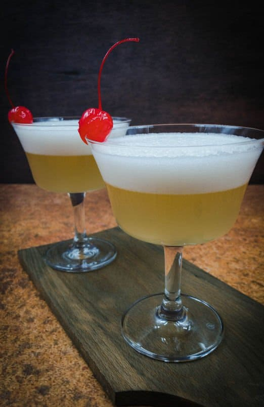 Two beautiful whiskey sour mocktails with a maraschino cherry garnish