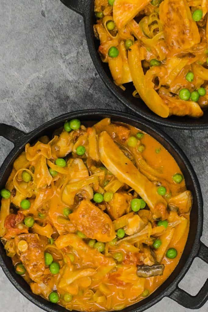Two cast iron dishes of halloumi stroganoff with mushrooms and peas