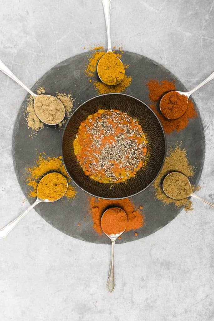 Indian curry spices on spoons on a slate