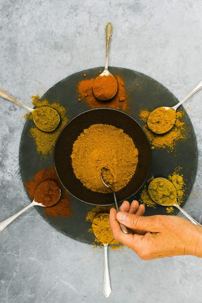 Someone mixing curry spices
