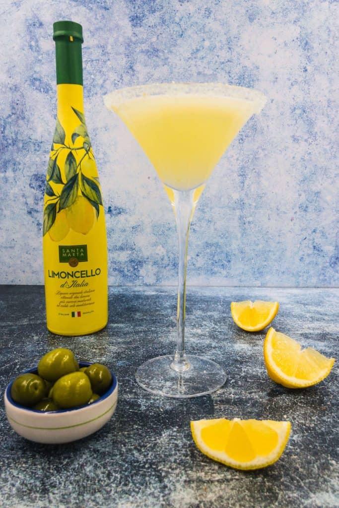 Limoncello bottle, lemon drop martini and wedges of lemon