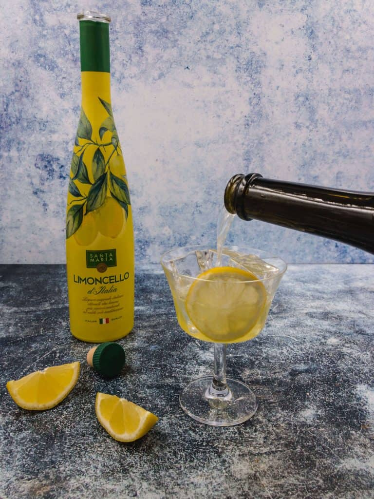 Pouring a spritz limoncello with wedges of lemon