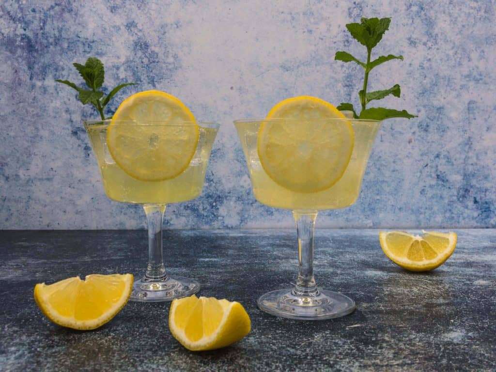 Two spritz limoncello cocktails, with mint and lemon slice and ice