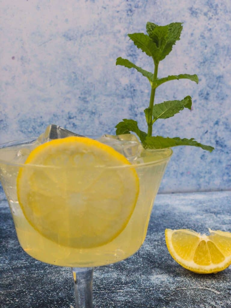 Close up of limoncello spritz cocktail with lemon, mint and ice