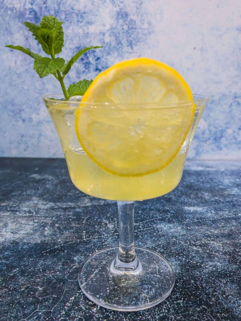 A glass of limoncello spritz with prosecco, club soda, ice, lemon and mint