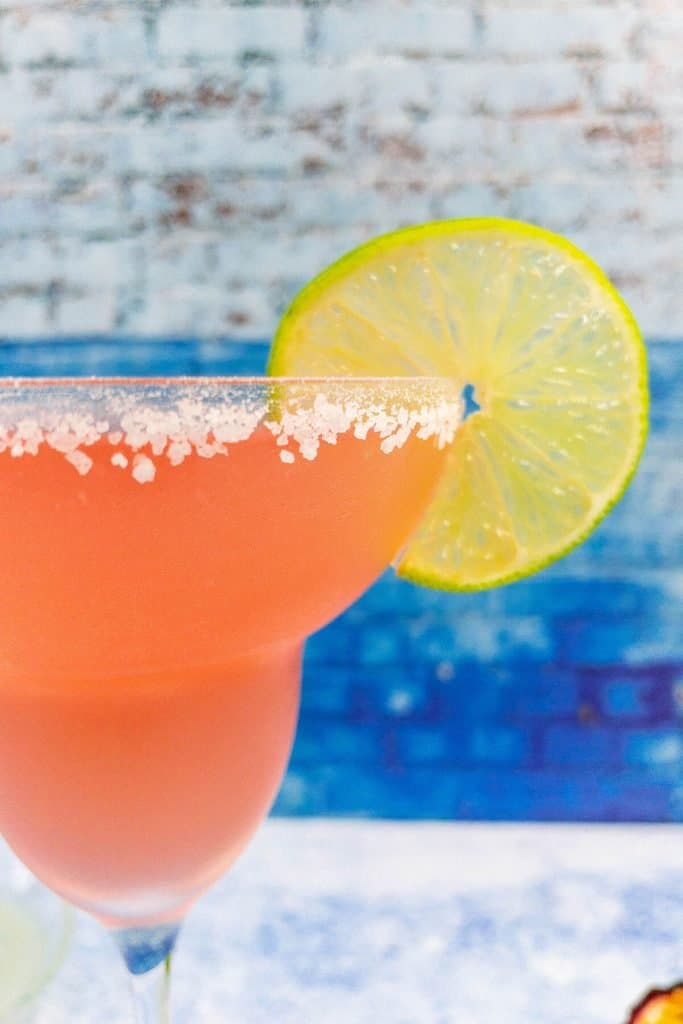 Close up of passion fruit margarita, salty rim and lime garnish