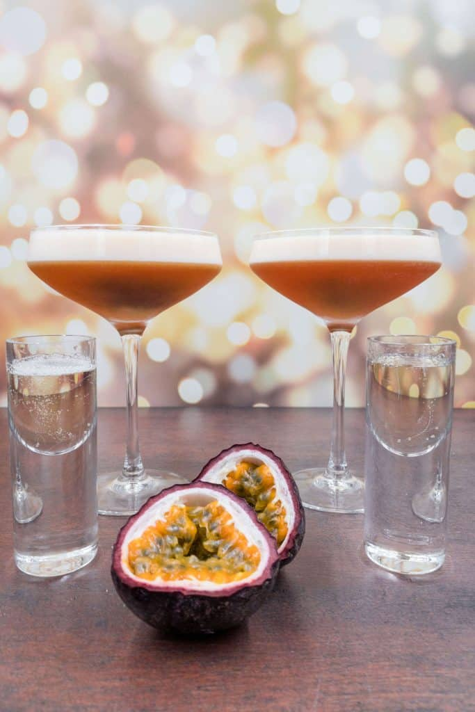 Two freshly made pornstar martinis with passion fruits and champagne shots