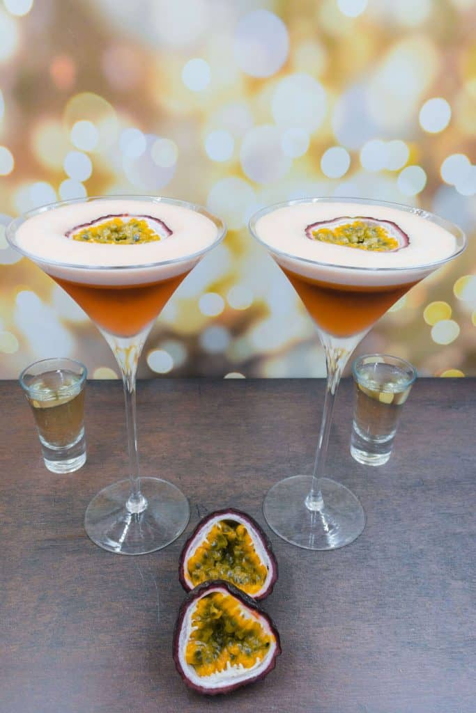 Two zero alcoholic pornstar martini cocktail drinks with half a fresh passion fruit as garnish