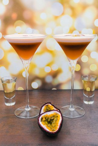 Two stunning alcohol free pornstar martini cocktail drinks with fresh passion fruit and a shot of alcohol free champagne
