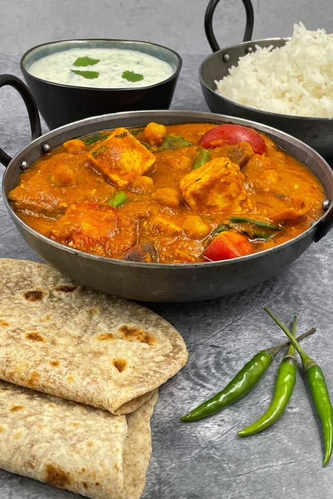 A bowl of curry by following homemade paneer jalfrezi recipe with chapatis, mint raita, rice and chilli peppers