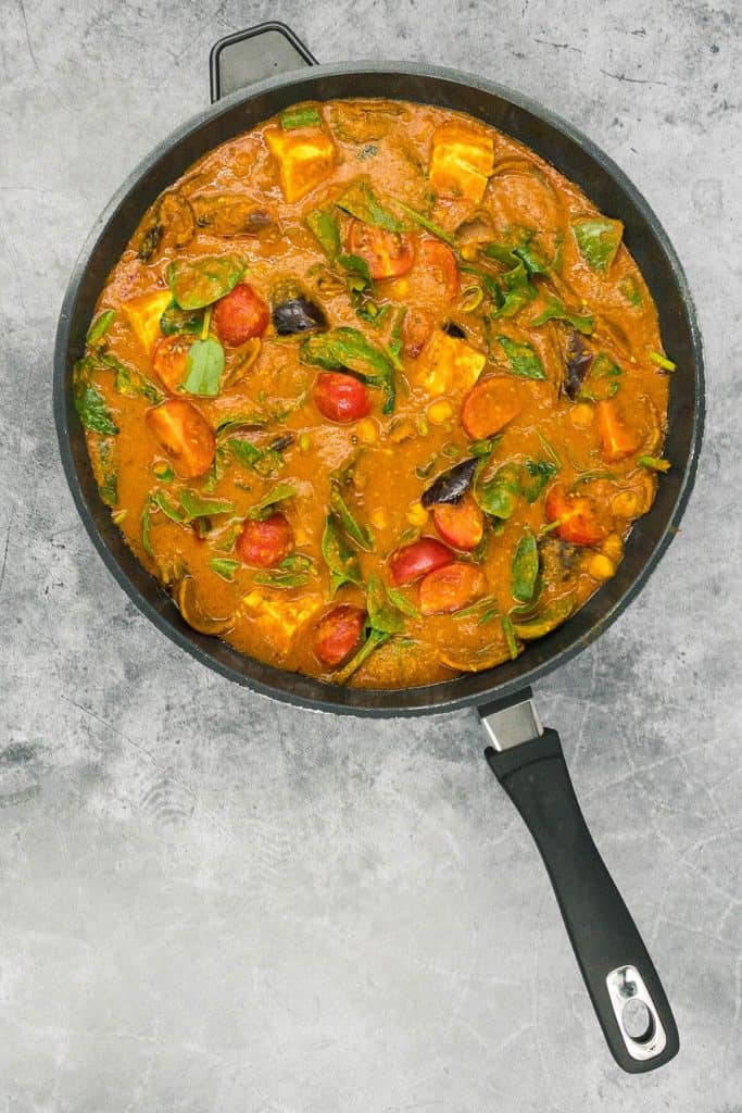A pan of freshly cooked paneer jalfrezi with tomatoes, spinach and onion