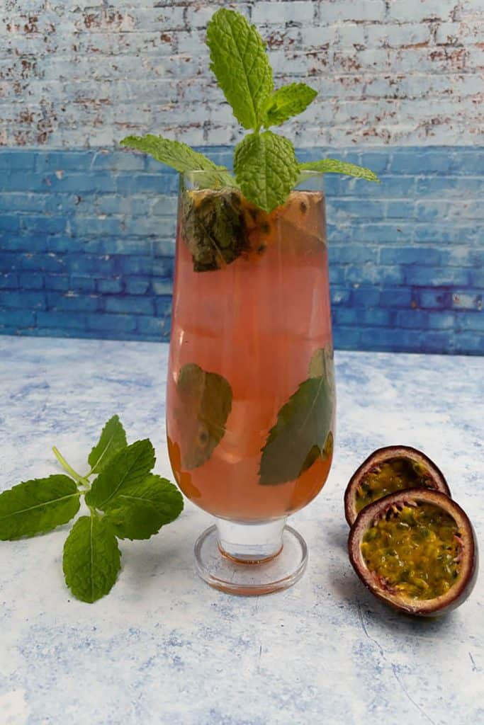 Fresh homemade delicious passion fruit mojito with mint leaves and fresh passion fruit in half
